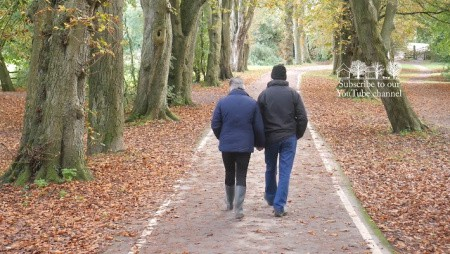 Couple walking through park in autumn with large trees and leaves on the ground.
