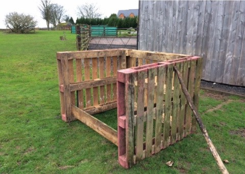Recycled pallets tied together to form a compost bin.